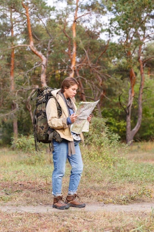 Una muchacha turística con una mochila que mira un mapa en un bosque del otoño fotos de archivo