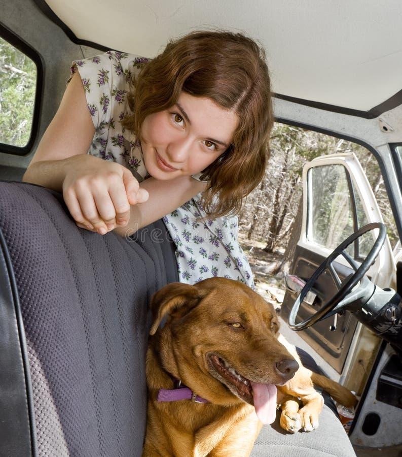 Una muchacha, un carro, y su perro fotografía de archivo