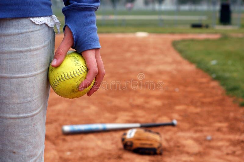 Una muchacha y su beísbol con pelota blanda, guante imagen de archivo libre de regalías