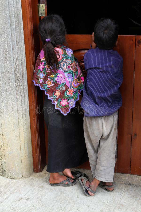Una muchacha y un muchacho indígenas del maya de Tzotzil en el vestido tradicional que mira en una casa en Zinacantan, México fotos de archivo libres de regalías