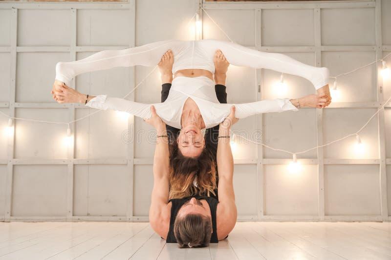 Una muchacha y una yoga del vapor de la práctica del hombre en un primer de textura brillante del estudio Meditación, mujer, homb fotos de archivo