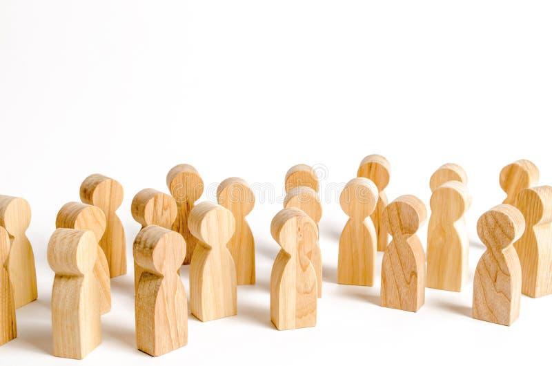 Una muchedumbre de figuras de madera de la gente en un fondo blanco Encuesta social y opinión pública, el electorado población fotografía de archivo libre de regalías