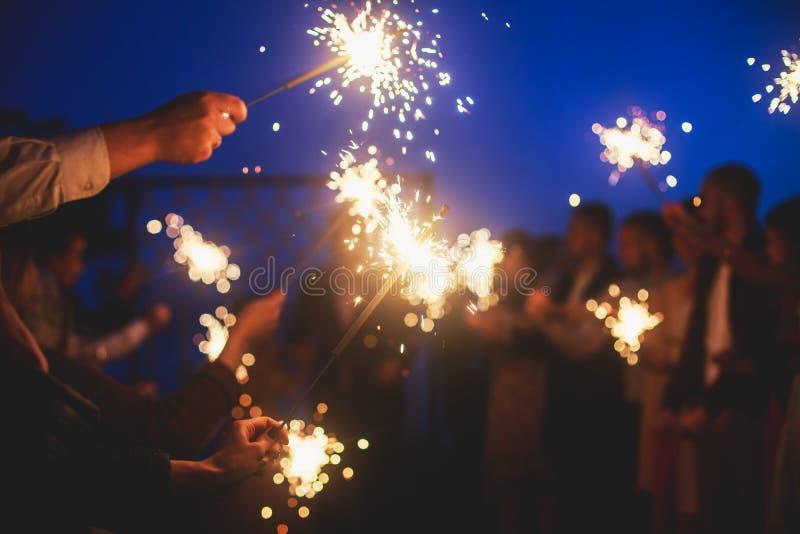 Una muchedumbre de gente feliz joven con Bengala enciende bengalas en sus manos durante la celebración del cumpleaños imagen de archivo