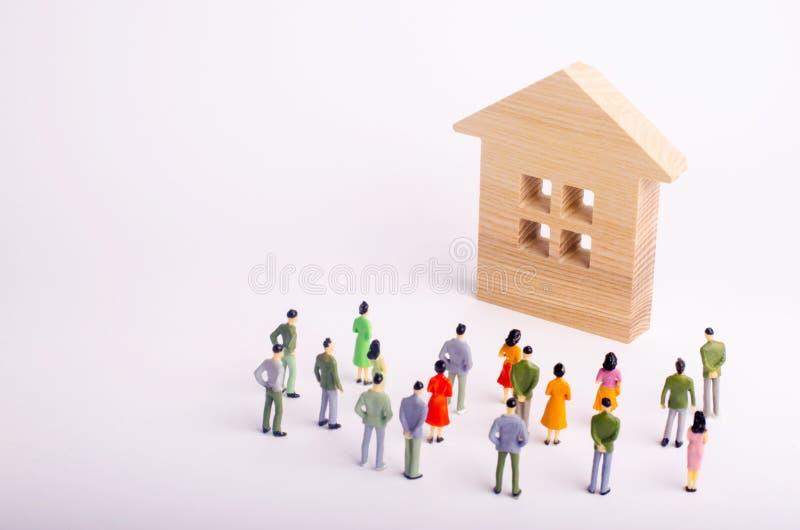 Una muchedumbre de gente que coloca y que mira una casa de madera en un fondo blanco Comprando y vendiendo de las propiedades inm imagen de archivo