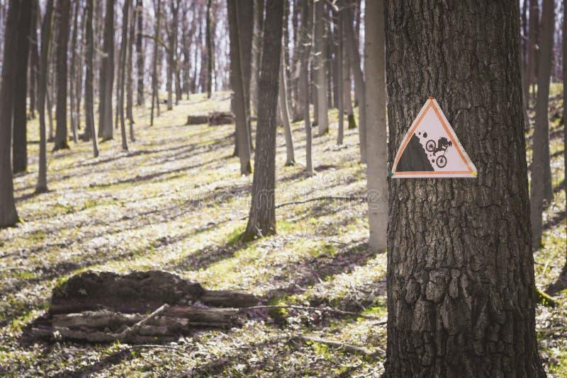 Una muestra en un árbol en la advertencia del bosque que hay un rastro para la pendiente extrema de bici-escaladores foto de archivo libre de regalías