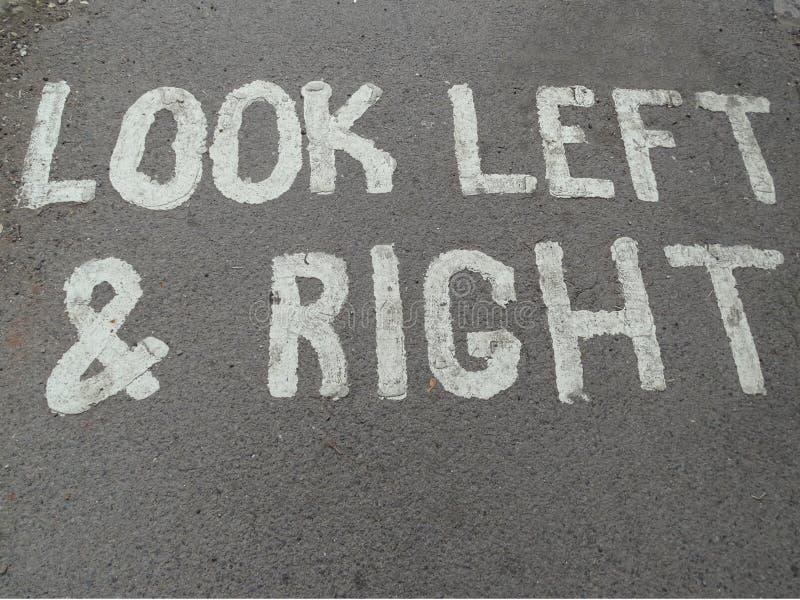 Una muestra pintada en una trayectoria concreta del pie que dice a gente mirar a la izquierda e a la derecha foto de archivo libre de regalías