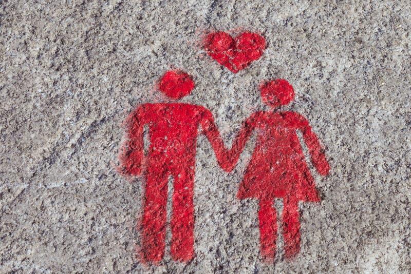 Una muestra roja se dibuja en la acera de Oporto: las manos del control del corazón, del hombre y de la mujer Una muestra del esp imágenes de archivo libres de regalías