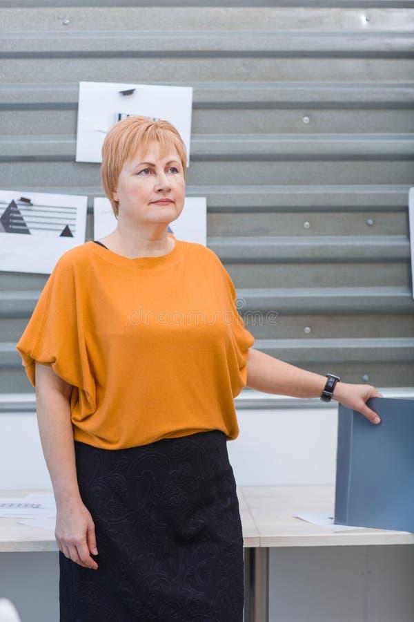 Una mujer adulta del oficinista se coloca con una carpeta cerca de la mesa foto de archivo