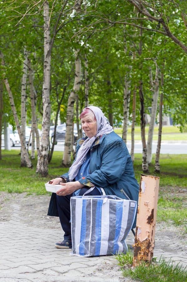 Una mujer adulta en bufanda pide donaciones Vista lateral foto de archivo libre de regalías