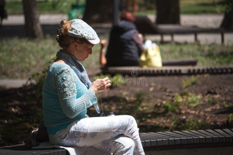 Una mujer adulta en un suéter y un casquillo hechos a mano hermosos se sienta en un banco en un parque de la ciudad y hace a ganc imagenes de archivo