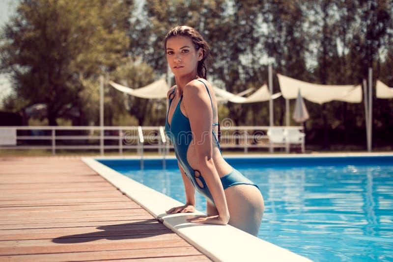 Una mujer adulta joven, presentando, borde de la piscina, saliendo el swimm imagen de archivo