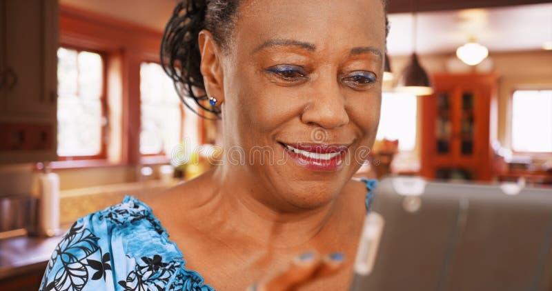 Una mujer afroamericana mayor utiliza su tableta en su cocina imagenes de archivo