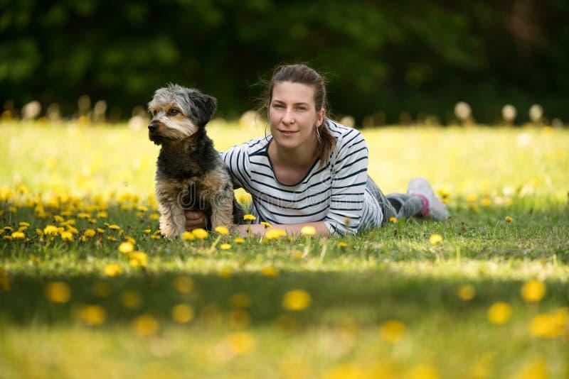 Una mujer alegre, joven que miente en la hierba con su animal doméstico foto de archivo libre de regalías