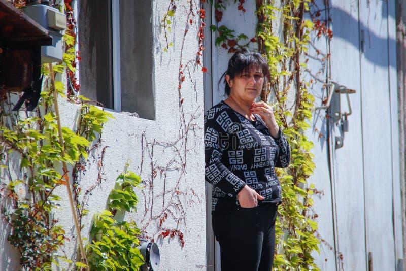 Una mujer armenia se coloca en su casa entrelazada con la hiedra y las uvas fotografía de archivo libre de regalías