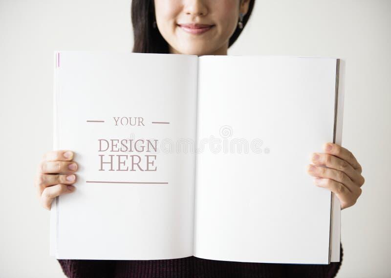 Una mujer asiática está sosteniendo una revista en blanco imagenes de archivo