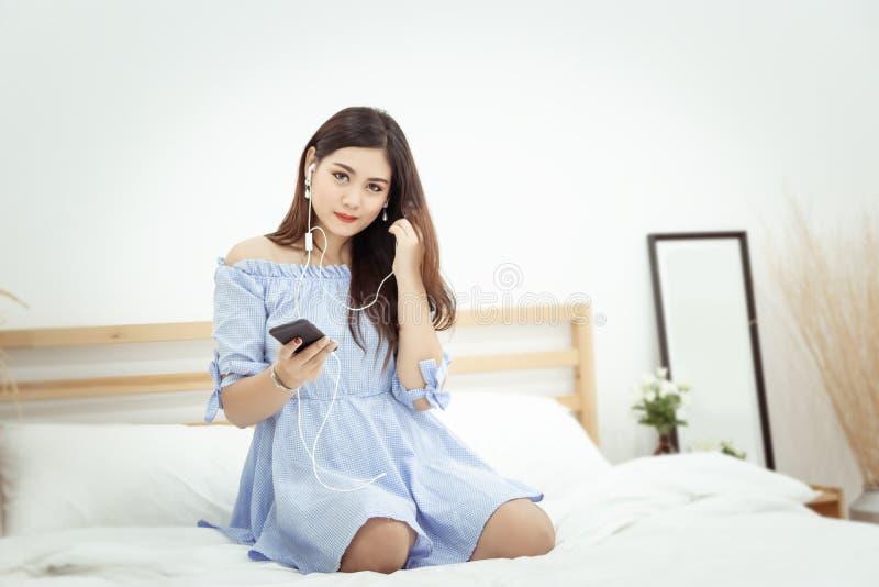 Una mujer asiática hermosa con el auricular que se relaja en casa, sentándose en la cama escuchando la música del uso en el teléf imagen de archivo