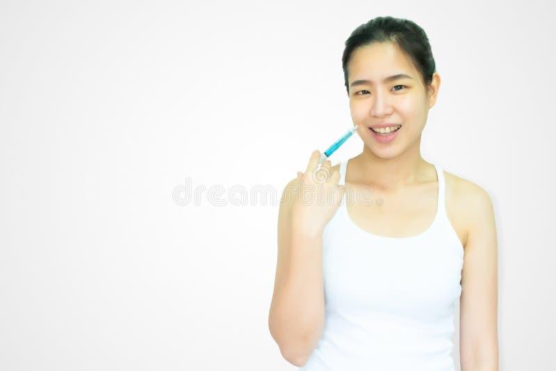 Una mujer asiática hermosa está haciendo el tratamiento del boton en el fondo blanco fotografía de archivo