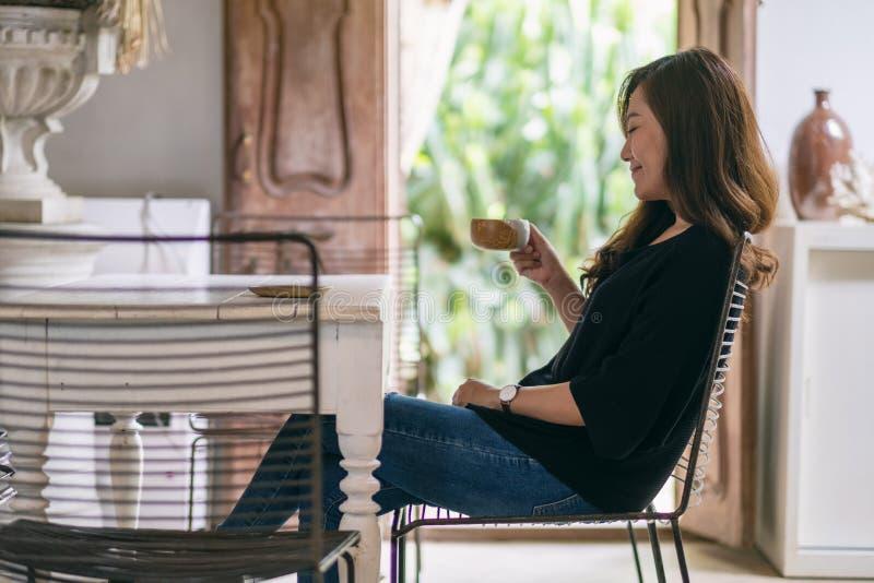 Una mujer asiática hermosa gozó el beber del café caliente en café imagenes de archivo