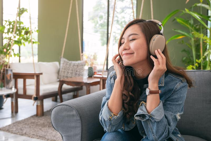 Una mujer asiática hermosa gozar el escuchar la música con el auricular imagen de archivo