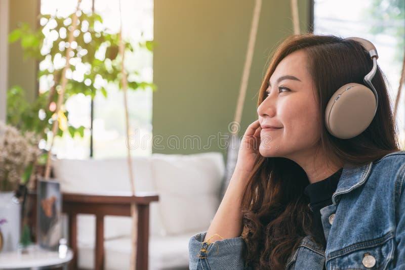 Una mujer asiática hermosa gozar el escuchar la música con el auricular fotografía de archivo