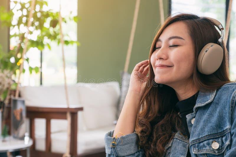 Una mujer asiática hermosa gozar el escuchar la música con el auricular fotos de archivo libres de regalías