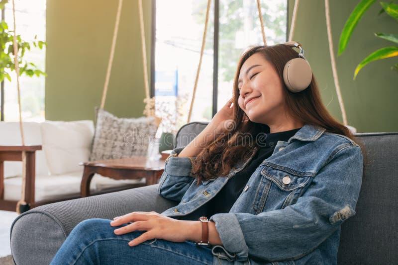 Una mujer asiática hermosa gozar el escuchar la música con el auricular fotografía de archivo libre de regalías