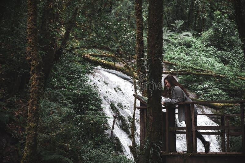 Una mujer asiática hermosa que se coloca delante de la cascada en bosque tropical fotografía de archivo
