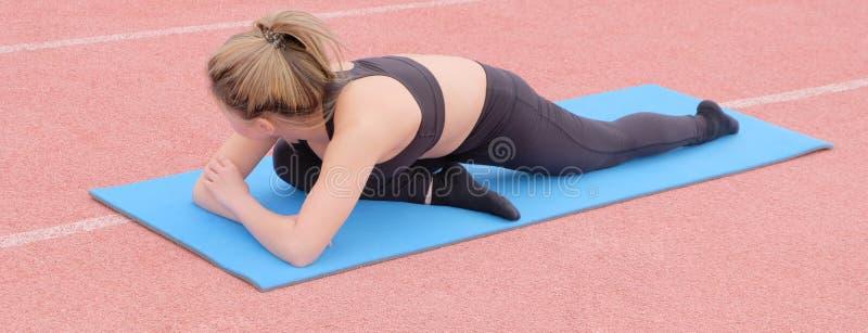 Una mujer asi?tica joven hermosa que hace un ejercicio para fortalecer los m?sculos de sus piernas en una estera de goma azul Est foto de archivo libre de regalías