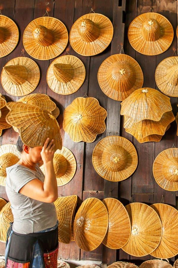 Una mujer asiática que elige el sombrero de un granjero que teje en tienda de souvenirs foto de archivo