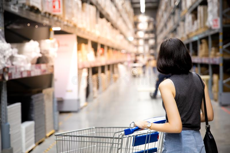 Una mujer asiática que hace compras y que camina con su carro en carg foto de archivo