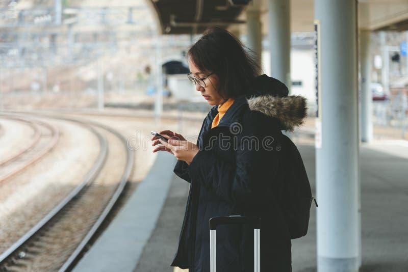 Una mujer asi?tica hermosa utiliza un smartphone en el centro de ciudad para buscar para los diversos lugares Estudios del restau fotos de archivo libres de regalías
