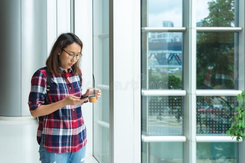 Una mujer asi?tica hermosa utiliza un smartphone en el centro de ciudad para buscar para los diversos lugares Estudios del restau imagen de archivo