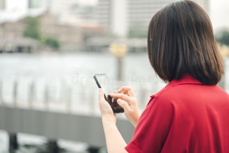 Una mujer asi?tica hermosa utiliza un smartphone en el centro de ciudad para buscar para los diversos lugares Estudios del restau fotos de archivo