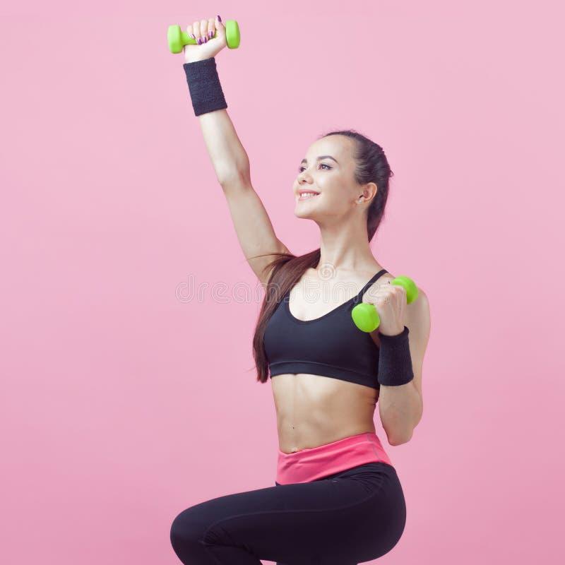 Una mujer atlética joven, con una sonrisa, en los deportes negros superiores, haciendo aeróbicos en fondo rosado con pesas de gim imagenes de archivo