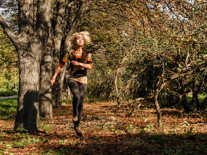 Una mujer atlética joven corre el salto en el parque y parece feliz fotografía de archivo