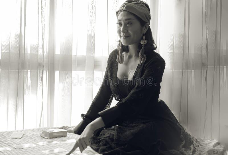 Una mujer atractiva con estilo gitano está haciendo adivinación fotografía de archivo