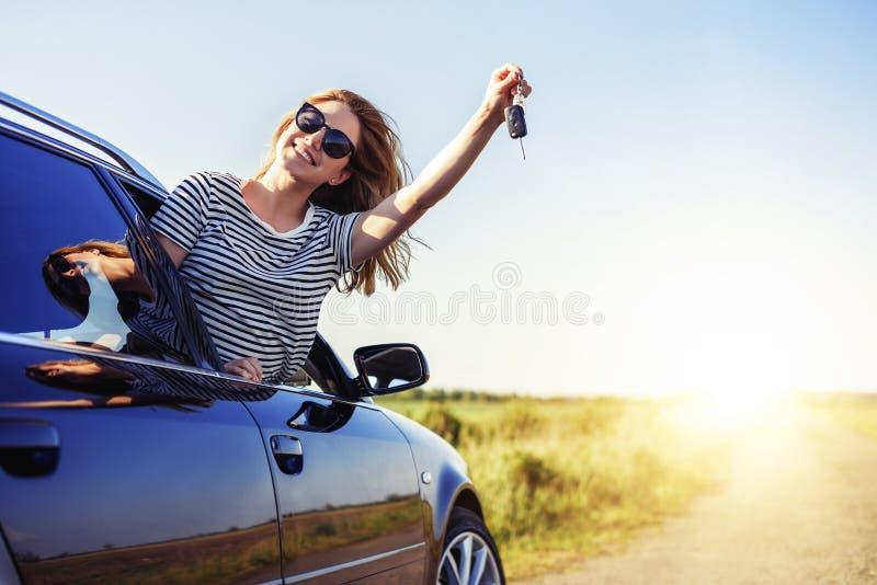 Una mujer atractiva en un coche lleva a cabo una llave del coche en su mano fotografía de archivo libre de regalías
