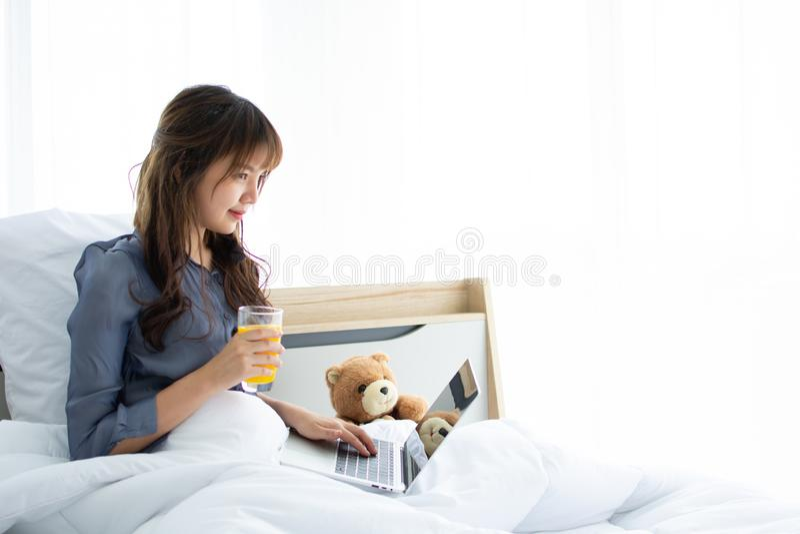 Una mujer atractiva está utilizando su ordenador portátil en su cama mientras que zumo de naranja de la bebida imagen de archivo