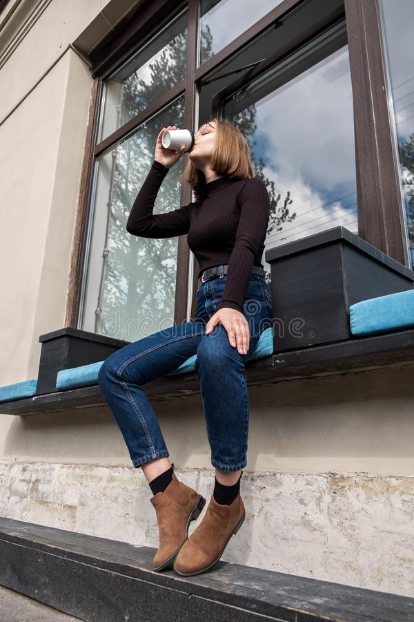 Una mujer atractiva joven con los vidrios se sienta en una ventana en un café de la calle fotos de archivo libres de regalías