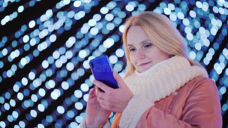 Una mujer atractiva joven utiliza un smartphone en el fondo de guirnaldas festivas en la ciudad foto de archivo