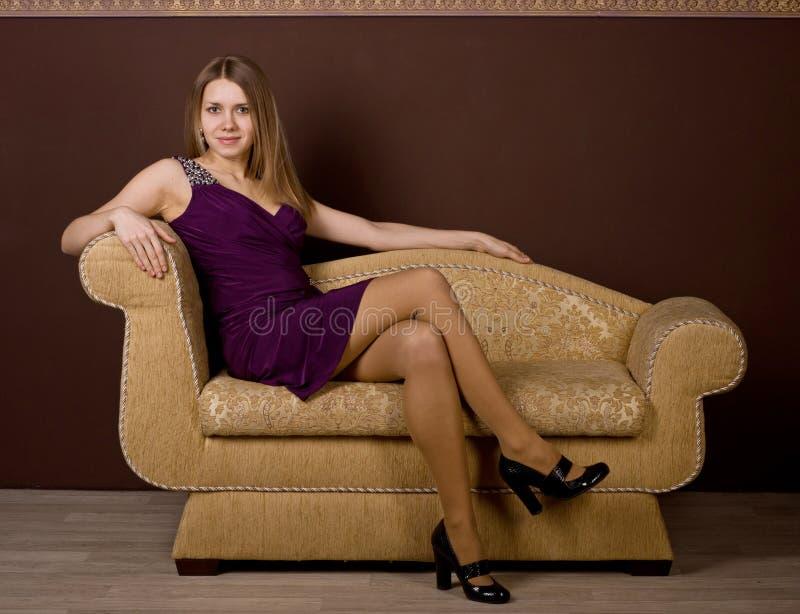 Una mujer atractiva que se sienta en el sofá fotografía de archivo libre de regalías