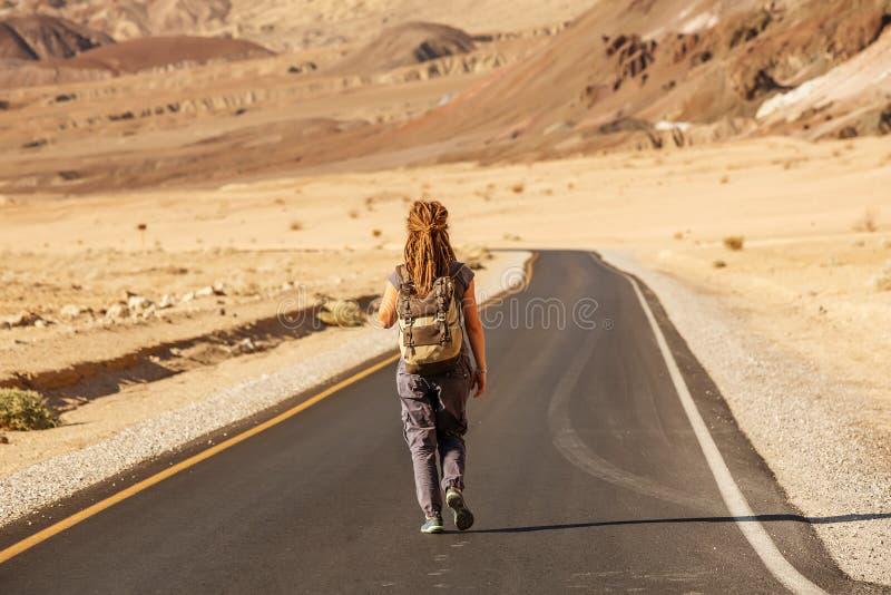 Una mujer autodidacta caminando por una carretera en Estados Unidos fotos de archivo libres de regalías