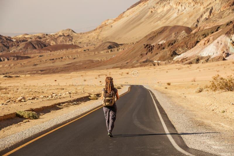 Una mujer autodidacta caminando por una carretera en Estados Unidos foto de archivo