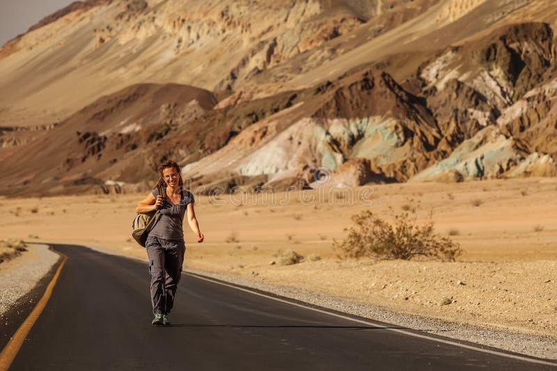 Una mujer autodidacta caminando por una carretera en Estados Unidos imagen de archivo