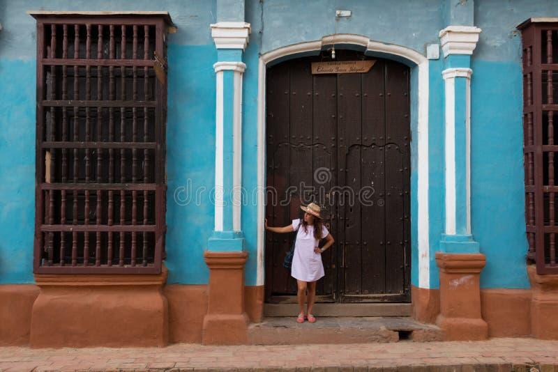 Una mujer bastante joven con el sombrero situado en la puerta de una casa colonial vieja en la ciudad colonial de Trinidad Cuba fotos de archivo libres de regalías