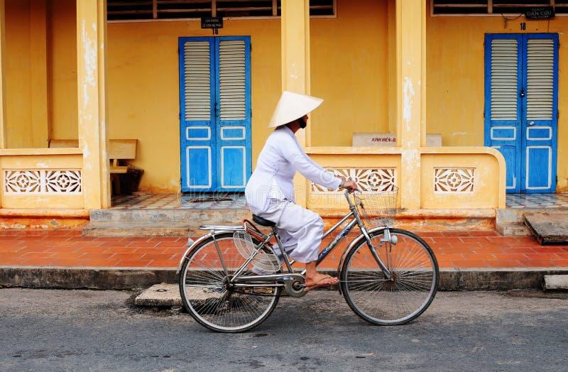 Una mujer biking en el camino rural en el delta del Mekong, Vietnam foto de archivo libre de regalías