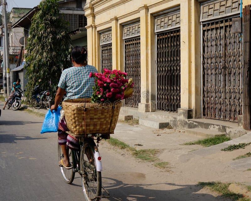 Una mujer biking en la calle en Bagan, Myanmar fotos de archivo libres de regalías