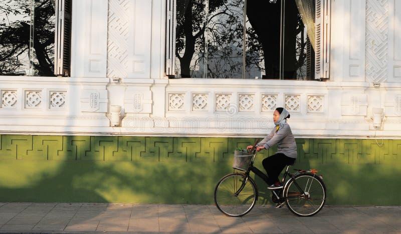 Una mujer biking en la calle en la ciudad vieja en Hanoi, Vietnam imagen de archivo libre de regalías