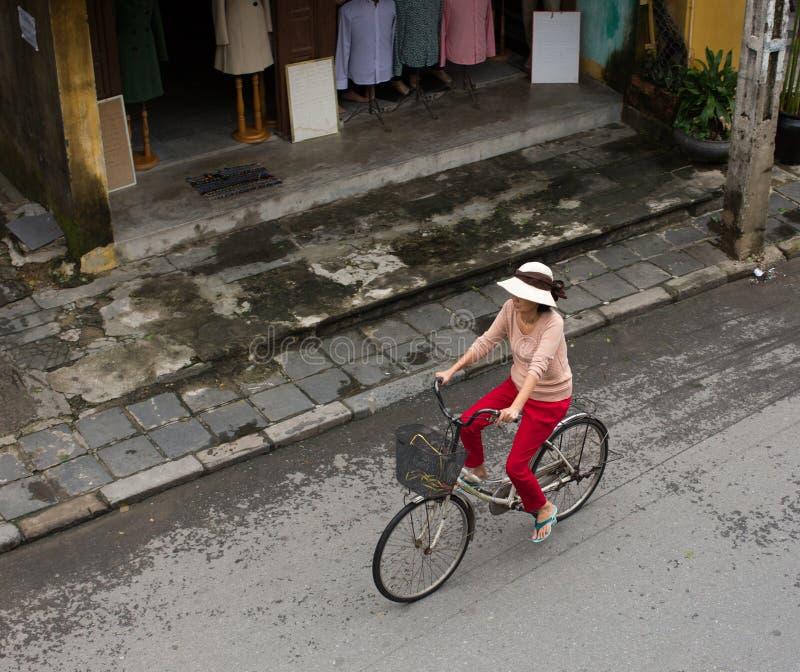 Una mujer biking en la calle en la ciudad vieja en Hoi An, Vietnam foto de archivo