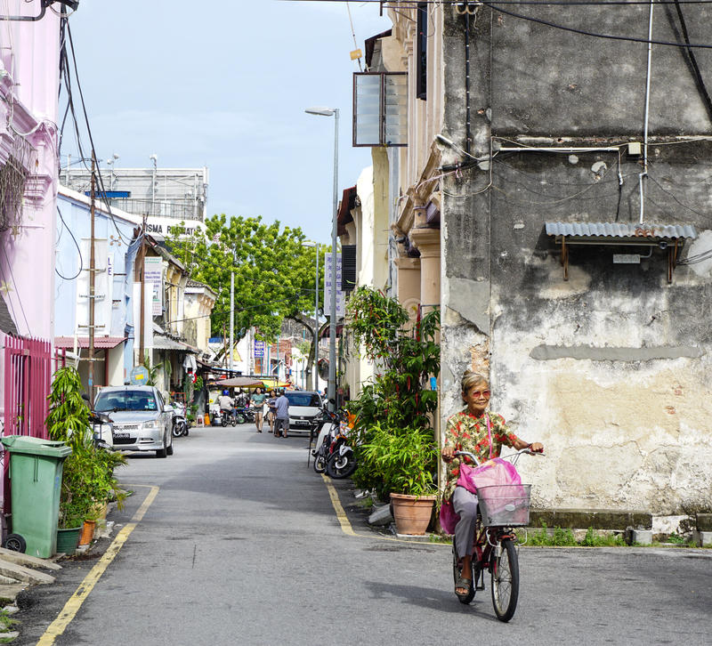 Una mujer biking en la calle en Penang, Malasia imagen de archivo libre de regalías